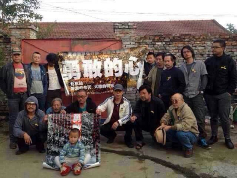A group photo of Songzhuang artists after an art performance. The small sign has messages in support of Hong Kong.
